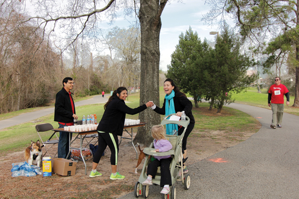 HAR Family Fun Run Event Chair Karishma Asrani hands out water to Fun Run Committee Member Courtney Katz at the water station which is manned by HAR Staff Member Patrick Partida and his dog Chelsea. Around the bend, strolls HAR's Director of Information Sam Scott. It was a true HAR Family Event on Saturday, February 22.